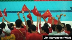 Chinese fans cheer at the Water Cube in Beijing.