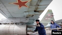 FILE - Servicemen load air-to-ground missiles onto a Sukhoi Su-25 jet fighter during a drill at the Russian southern Stavropol region, March 12, 2015.