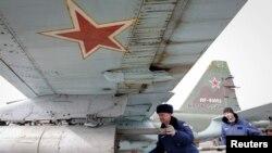 俄罗斯在该国南部以及在从乌克兰吞并的克里米亚等地区进行军事演习,俄罗斯军人正在往苏-25战机上装载空对地导弹(2015年3月12日)
