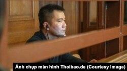 Bị cáo Nguyễn Hải Long ngồi trong phòng kính chống đạn tại tòa Thượng thẩm Berlin. (Ảnh chụp màn hình Thoibao.de)