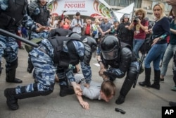 Police detain a protester in Moscow, Russia, June 12, 2017.