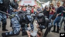 Полиция задерживает демонстранта во время протестов в Москве 12 июня 2017 года