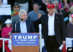 Republican presidential candidate Donald Trump, right, stands next to Sen. Jeff Sessions, R-Ala., as Sessions speaks during a rally in Madison, Alabama, Feb. 28, 2016.