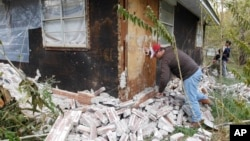 Chad Devereaux works at cleaning up the bricks that fell from three sides of his in-laws home in Sparks, Oklahoma, Nov. 6, 2011, after two earthquakes hit the area in less than 24 hours.