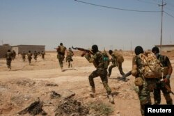 FILE - Asaib Ahl al-Haq Shi'ite militia fighters from the south of Iraq run during a mission to take control of Sulaiman Pek village from Islamist State militants, in the northwest of Tikrit city, Sept. 1, 2014.