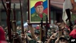 Miembros de la Milicia Nacional Revolucionaria, también llamados fuerzas bolivarianas, levantan sus armas como homenaje al presidente de Venezuela, Hugo Chávez.