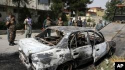 Abashinzwe umutekano barareba imodoka yatwitswe na za roketi mu murwa mukuru Kabul w'Afuganisitani