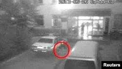 A man attacks a vehicle parked outside an office building of a special patrol squadron at Lukqun Township in northwest China's Xinjiang Uygur Autonomous Region in this image released by CCTV, June 26, 2013.