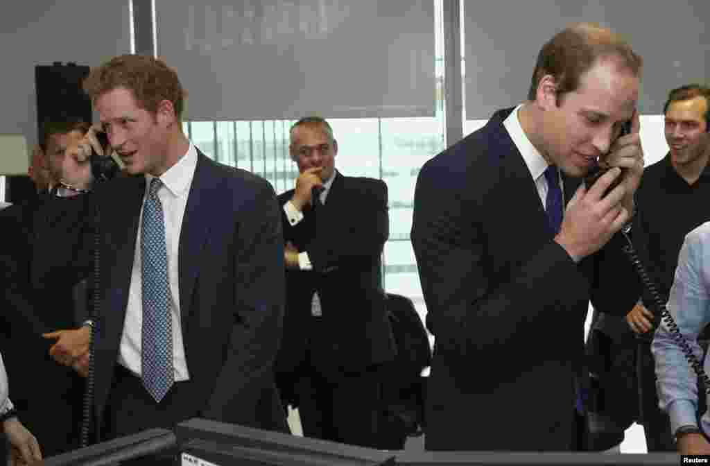 Britain's Prince Harry (L) and Prince William (R) take part in a trade on the trading floor of BGC Partners. BGC holds a Charity Day each year to commemorate the 658 employees who lost their lives in the 9/11 attacks on the World Trade Centre in New York. London, September 11, 2013.