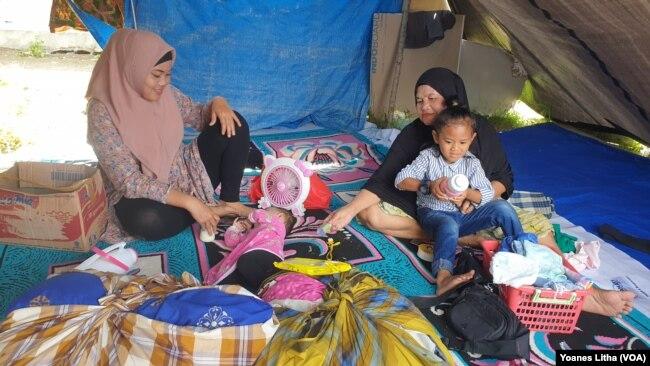 Seorang ibu menidurkan anak balitanya di dalam tenda terpal di Posko Pengungsian Buah Hati, Kelurahan Karema, Kota Mamuju, Sulawesi Barat. Selasa (26/1/2021). (Foto: VOA/Yoanes Litha)