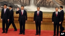 Chinese President Xi Jinping, third from left, waves as he walks in with other members of the Chinese Politburo Beijing's Great Hall of the People, Oct 25, 2017.