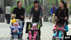 FILE - Women push babies in strollers through a Beijing park during a public holiday.
