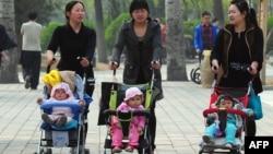 Para Ibu mendorong anaknya di kereta dorong di Beijing (5/4/2011). Kebijakan satu anak yang telah diberlakukan puluhan tahun akan dilonggarkan di China.