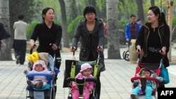 FILE - Women push babies in prams through a Beijing park during a public holiday, April 5, 2011.