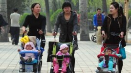 Women push babies in prams through a Beijing park during a public holiday, April 5, 2011.