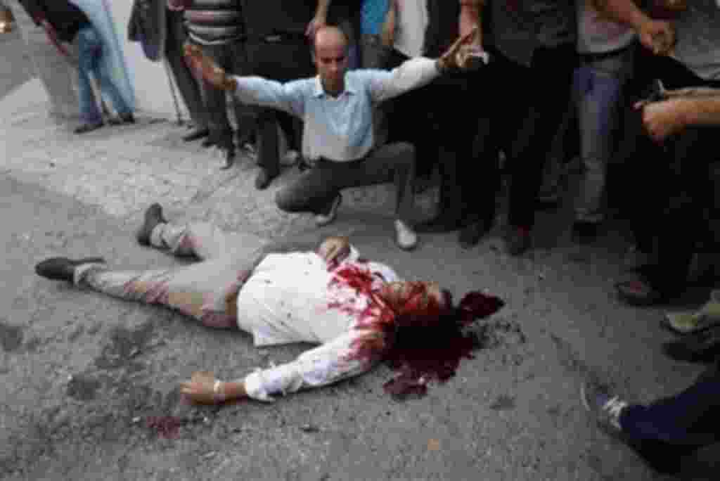 ** EDS NOTE GRAPHIC CONTENT ** Onlookers observe the body of a man allegedly shot by pro-government militia near a rally supporting leading opposition presidential candidate Mir Hossein Mousavi in Tehran, Iran, Monday, June 15, 2009. Hundreds of thousand