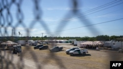 FILE - United States Border Patrol vehicles and temporary structures are pictured under the Del Rio Port of Entry during its reopening after being closed for over a week due to an influx of migrants, Sept. 25, 2021.