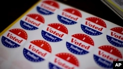 FILE - Stickers wait for voters at a polling place in Philadelphia, Nov. 5, 2013.