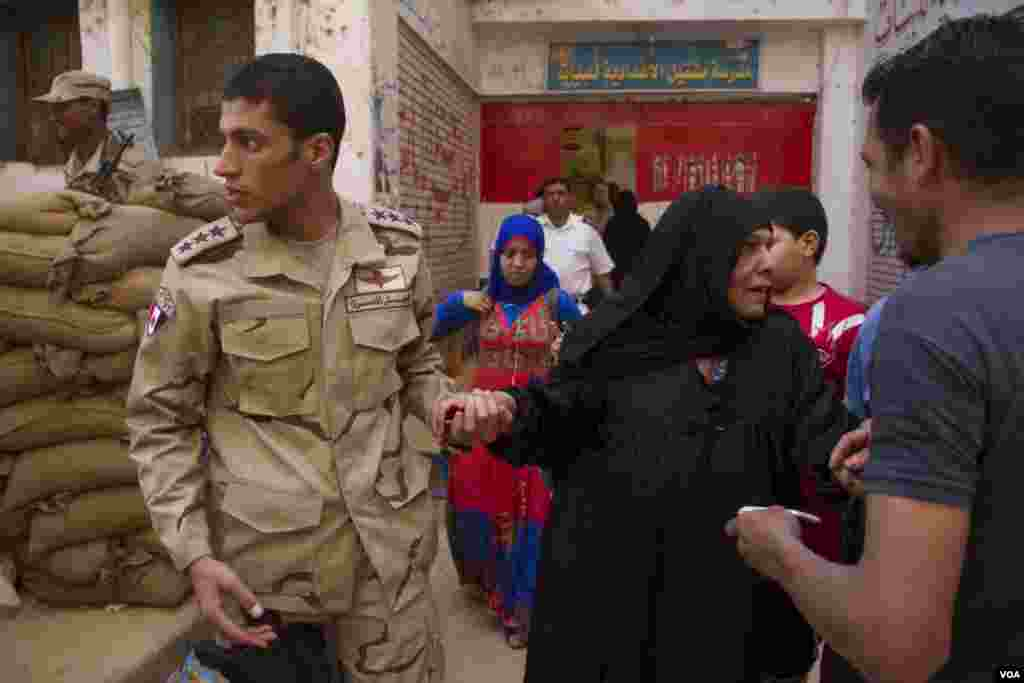 A soldier helps a woman at a polling station in Cairo, May 27, 2014. (Hamada Elrasam /VOA)