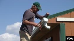 Ông Jack Rose cài đặt máng xối trên mái nhà tại trang trại White Plume