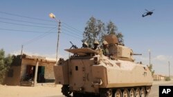 FILE - In this Tuesday, May 12, 2013 file photo, Egyptian Army soldiers patrol in an armored vehicle backed by a helicopter gunship during a sweep through villages in Sheikh Zuweyid, north Sinai, Egypt. An Egyptian militant group affiliated with the Islam