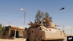 Photo d'archives – Des soldats de l'armée égyptienne effectuent des patrouilles dans un véhicule blindé, soutenus par un hélicoptère dans le nord du Sinaï, en Égypte (12 mai 2013).