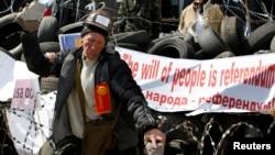 一名親俄抗議者4月15日在烏克蘭東部一座政府大樓外用石塊砸牆