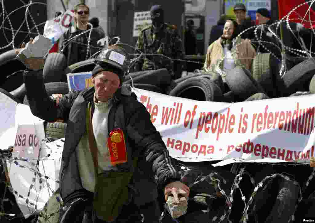 A pro-Russia protester breaks a piece of stone at a barricade outside a regional government building in Donetsk, in eastern Ukraine, April 15, 2014.