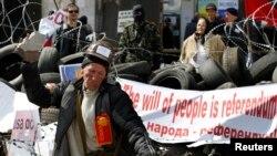 一名亲俄抗议者4月15日在乌克兰东部一座政府大楼外用石块砸墙