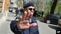 FILE - Bosnian police are seen securing an area around a government building during an investigation, in the capital Sarajevo, April 26, 2013.