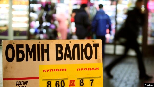 FILE - A display shows currency exchange rates in central Kyiv, Ukraine, Feb. 4, 2014.