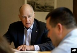California Gov. Jerry Brown discusses a bill with budget analyst Chris Ferguson, right, in Sacramento, Calif., July 7, 2017.
