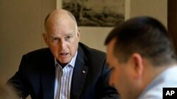 FILE - California Gov. Jerry Brown discusses a bill with budget analyst Chris Ferguson, right, in Sacramento, California, July 7, 2017. Brown and legislative leaders released a plan Monday to extend through 2030 California's cap-and-trade program, a key piece of the state's quest to fight climate change by drastically reducing emissions from greenhouse gases.