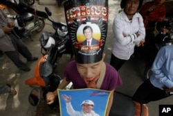 FILE - A supporter of the now dissolved opposition Cambodia National Rescue Party wears a poster of party leader Kem Sokha as she stands outside the Supreme Court in Phnom Penh, Cambodia, Oct. 31, 2017.