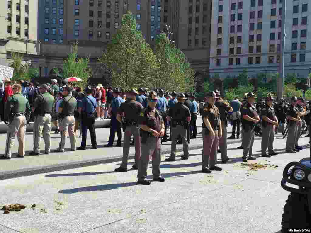 State troopers and police officers stand in lines around the protesters as tensions rose, near the Soldiers and Sailors Monument in Public Square, in Cleveland, July 19, 2016.