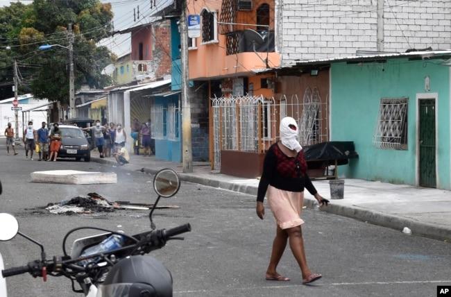 Una mujer camina con un pañuelo en la cabeza para evitar el olor del cadáver de una persona que presuntamente falleció de la COVID-19 en Guayaquil, Ecuador, el 3 de abril de 2020.