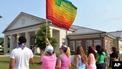 Manifestantes ondean una bandera gay frente al Centro Judicial del condado de Rowan, en Kentucky.