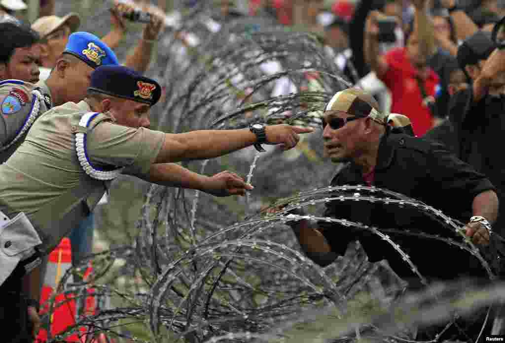 An Indonesian policeman argues with a supporter of presidential candidate Prabowo Subianto during a protest near the Constitutional Court in Jakarta. Police fired tear gas to disperse thousands of protesters outside the country's top court in Jakarta, as judges started delivering their verdict into last month's disputed presidential election.