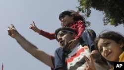A Syrian family shouts anti-Syrian President Bashar Asssad slogans as they wear Syrian independence flags during anti-Syrian regime protest outside the Arab League headquarters in Cairo, Egypt, July 3, 2011
