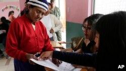 Seorang pemilih berbincang dengan petugas pemungutan suara dalam referendum konstitusional yang diajukan oleh Presiden Lenin Moreno di Quito, Ekuador, Minggu, 4 Februari 2018.