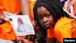 一名莫桑比克小女孩揮舞印有教宗方濟各畫像的旗子歡迎到訪首都馬普託的教宗。 (2019年9月5日)