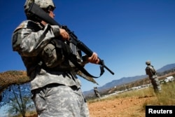 FILE - United States National Guard troops patrol along the U.S. and Mexico border in Nogales, Arizona, Oct. 8, 2010.