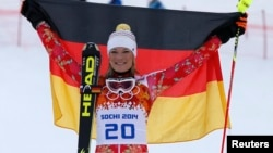 Germany's winner Maria Hoefl-Riesch poses with a German flag during the flower ceremony after competing in the slalom run of the women's alpine skiing super combined event during the 2014 Sochi Winter Olympics on Feb. 10, 2014.