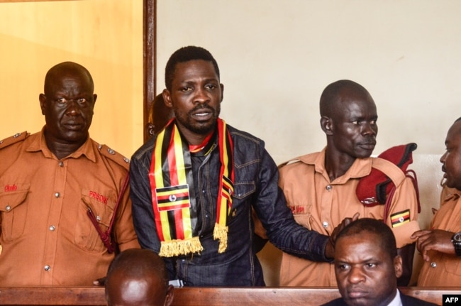 Prominent opposition politician Robert Kyagulanyi known as Bobi Wine (2L) appears at the chief magistrate court in Gulu, northern Uganda, Aug. 23, 2018.