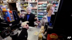 Cashiers Kathy Robinson, left, and Ethel Kroska, right, both of Merrimack, New Hampshire, sell lottery tickets Sunday, Jan. 7, 2018, at Reeds Ferry Market convenience store, in Merrimack. (AP Photo/Steven Senne)