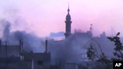 In this image made from amateur video released by the Shaam News Network and accessed June 25, 2012, smoke rises from buildings following purported shelling in Talbeesa, Homs, Syria. (AP cannot independently verify the content, date, location or authenticity of this material.)