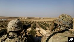 ABŞ hərbi qüvvələrinin əsgərləri Suriyada Manbic şəhərindəki postda ərazini izləyir.