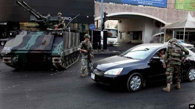 Lebanese Army soldiers check a car in the northern city of Tripoli