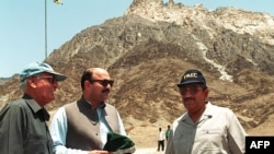 پاکستان کے ایٹمی سائنس دان ثمر مبارک (دائیں)، ایٹامک انرجی کمیشن کے چیئرمین ڈاکٹر اشفاق احمد (بائیں)، وزیرِ اطلاعات مشاہد حسین سید بلوچستان کے ضلع چاغی میں اس پہاڑ کے قریب موجود ہیں جہاں پانچ ایٹمی دھماکے کیے گئے تھے۔
