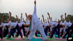 Prime Minister Narendra Modi performs yoga along with thousands of Indians on Rajpath in New Delhi, June 21, 2015.